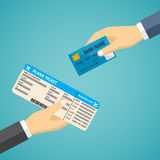Hand with credit card and hand with boarding pass. Royalty Free Stock Image