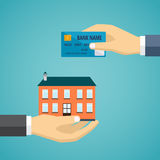 Hand with credit card and hand with house. Royalty Free Stock Photos