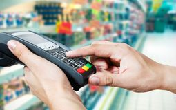 Hand with credit card swipe through payment terminal. Hand with credit card swipe through terminal for sale in supermarket Stock Photography