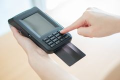 Hand with credit card swipe through terminal. Isoleat stock photos