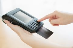 Hand with credit card swipe through terminal. Isoleat stock photography