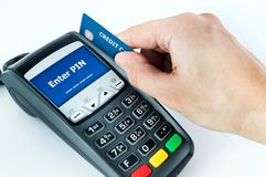 Hand with credit card swipe through terminal for sale. Enter PIN on display royalty free stock image