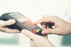 Hand with credit card swipe through terminal for sale in superma Royalty Free Stock Images