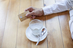 Hand with credit card to pay coffee. Woman with white shirt ready to pay empty finished cappuccino coffee cup with made up credit card in hand on light brown Royalty Free Stock Photo