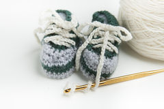 Hand crocheted baby shoes with wool, crochet needle Royalty Free Stock Photo