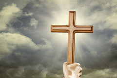 Hand with cross over the sky Royalty Free Stock Photo