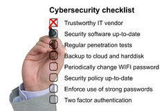 Hand crosses off the first item of a cybersecurity checklist Stock Photo