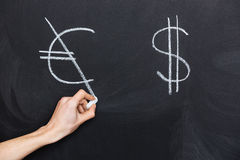 Hand crossing dollar and euro signs on blackboard Stock Photos