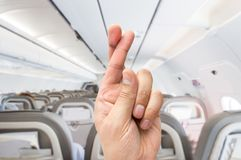 I need good luck in my flight. Hand crossing the fingers like symbol of superstition to have good luck at the indoor of the plane Stock Photography