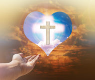 Hand with crucifix and light on heart background Stock Image