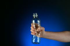A hand crushing a recyclable plastic bottle Royalty Free Stock Photography