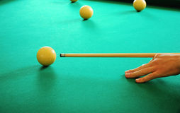 Hand with a cue and billiards balls Stock Images