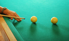 Hand with a cue and billiards balls Stock Photography