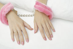Hand cuffs. Beautiful female hands locked in the pink handcuffs on the sheets Stock Photos