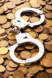Hand cuffs and coins. As security concept Royalty Free Stock Photo