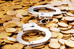Hand cuffs and coins. As security concept Stock Photo
