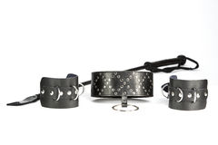 Hand cuffs, collar and whip made of black leather Stock Photo