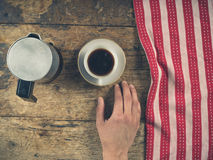 Hand with cup of coffee and tea towel on wood Royalty Free Stock Photos