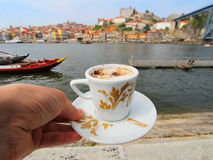Hand with a cup of coffee and view of Douro riverside from the Dom Luiz bridge , Porto , Portugal. Stock Photo