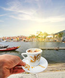 Hand with a cup of coffee and view of Douro riverside from the Dom Luiz bridge , Porto , Portugal. Royalty Free Stock Photo