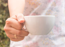 Hand on cup of coffee with vintage filter Stock Photos