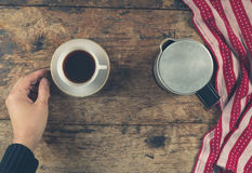 Hand with cup of coffee on wood Stock Images