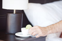 Hand, a cup of tea on the bedside table and lamp. Man hand, a cup of tea on the bedside table and lamp Stock Photography