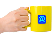 Hand and cup of tea with at symbol Stock Photography