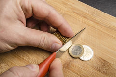 Hand cut euro coins with a knife on a cutting board. Separating them as pieces of food royalty free stock photography