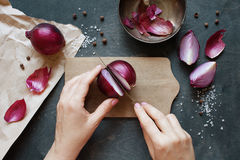 Hand cut red onion. In the kitchen Royalty Free Stock Photography