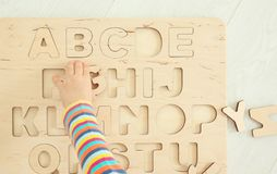 Hand of cute little child playing with letters. At home stock images