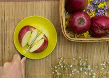 Hand cuts fruit by knife. Hand holds knife and cuts red apple on two parts at yellow dish near basket stock photography