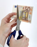Hand cutting a banknote Stock Images