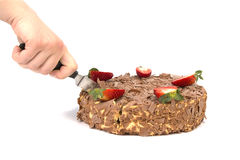 Hand cutting chocolate cake with strawberries on white Royalty Free Stock Images