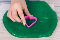 Hand cutting a green slime with purple plastic heart cookie cutter on a table.  royalty free stock photos