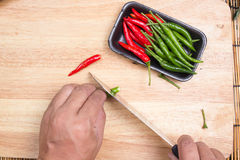 Hand cutting Hot Chili Peppers Royalty Free Stock Image