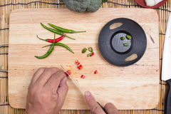 Hand cutting Hot Chili Peppers Royalty Free Stock Images