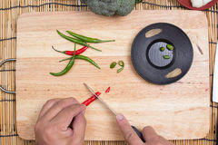 Hand cutting Hot Chili Peppers Stock Photos