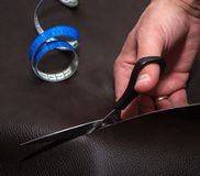 Hand cutting leather using scissors and twisted blue tape measure royalty free stock images