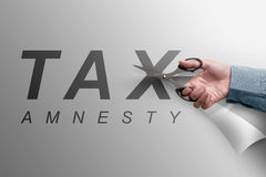 The hand cutting the paper that reads tax amnesty Stock Image