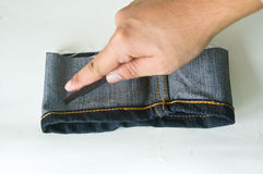 Hand cutting piece of jeans Stock Images
