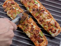 Hand cutting pizza baguette with mozzarella, green pepper, onion Stock Photo