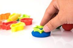Hand cutting play dough via plastic block Royalty Free Stock Photo