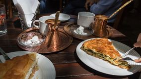 Spanakopita and greek coffee. Hand cutting a portion of spanakopita, a greek traditional spinach pie on a table with copper pot with coffee, outdoors Royalty Free Stock Images