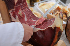 A hand cutting prosciutto Stock Photo