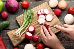 Hand cutting radishes. Female hand cutting fresh radishes on brown board Royalty Free Stock Images