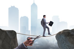 The hand cutting the rope under businessman tightrope walker Royalty Free Stock Image