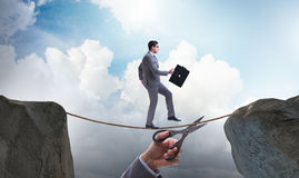 The hand cutting the rope under businessman tightrope walker Royalty Free Stock Photo