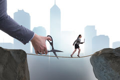 The hand cutting the rope under businesswoman tightrope walker Royalty Free Stock Images