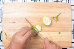 Hand cutting Thai Brinjal on wooden broad Stock Photo
